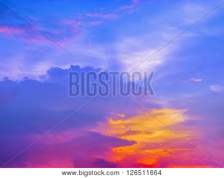 Colorful Sunset with multiple colors of sunlight glow over the country side with a silhouette of coconut trees at the horizon. ** Note: Visible grain at 100%, best at smaller sizes