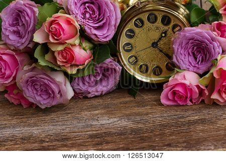 bouquet of pink and violet  fresh roses with golden vintage clock