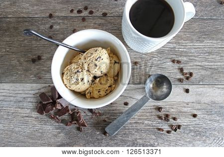 Overhead view of a bowl of coffee ice cream, cup of coffee, chocolate, coffee beans and vintage ice cream scoop
