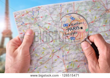 Man Consulting A Map Of Paris With A Magnifying Glass