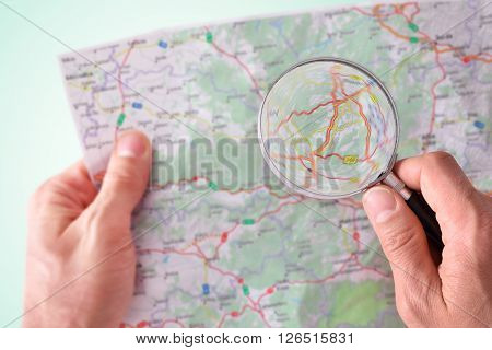 Man Consulting A Map With A Magnifying Glass