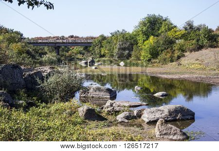 the small still hush river with stones on the bank and small bridge in background