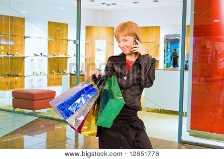 """a girl with shopping bags in a mall is talking on a cell phone  - See similar images of this """"Gorgeous shopping women"""" series in my portfolio"""
