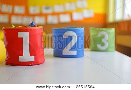 Red Green And Blue Jars With Written One Two And Three On The Table In The Kindergarten Classroom