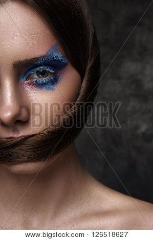 Half Face of beauty Model with blue Makeup on Eyes and creative Hairstyle