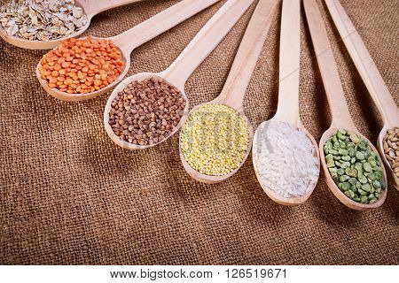 Grains in the spoon, a wooden spoon, a range of cereals, cereals with spoon on cloth, grain yield, organic food, cereal close-up, texture of burlap, kitchen utensils, healthy food.