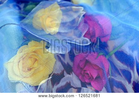 Yellow and pink roses on a leopard pattern scarf beneath a blue scarf with a pattern of roses decorations flowers