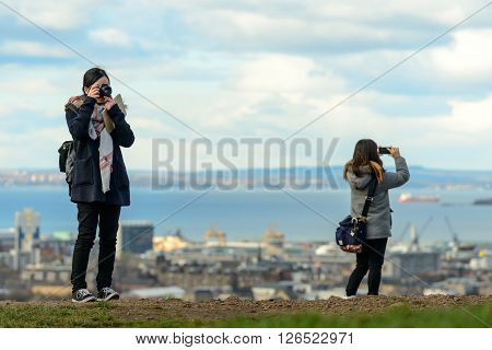 EDINBURGH SCOTLAND UK - 16 MARCH 2016: Two females tourists taking photos from the vantage point of Calton Hill in Edinburgh.