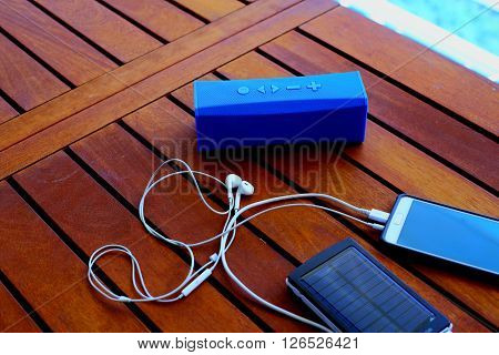 solar battery charges the phone that plays music through the speaker on a wooden table