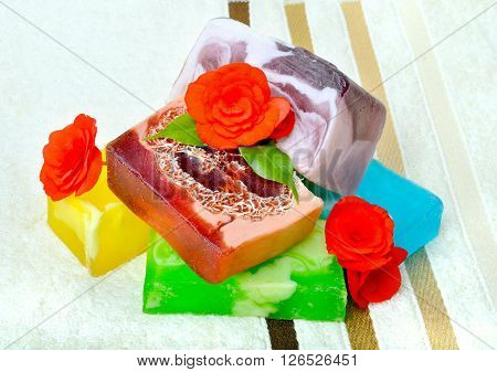 Handmade soap with flowers on a background colored towels.