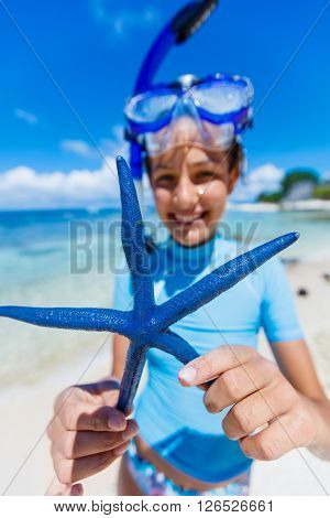 Girl holding a blue starfish, Philippines. Focus on the starfish