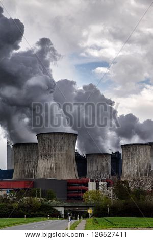steaming cooling towers of a power plant with dark gray emissions behind a small country road. concept for industry co2 and environmental protection vertical