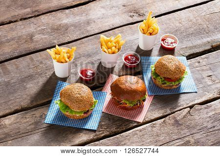 Hamburgers and fries with ketchup. Table with fast food meal. Freshly cooked junk food menu. High-calorie food in cafe.
