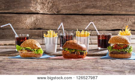 Burgers and glasses with cola. Food and cola on table. Meal of holiday season. Breakfast in local bistro.