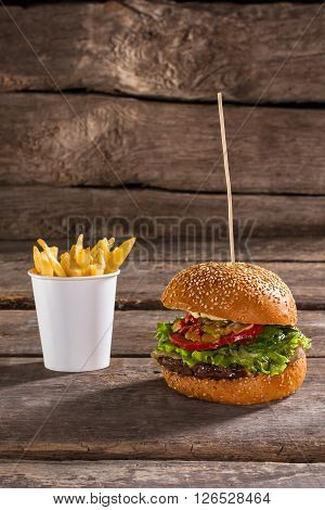 Fries and burger on stick. Old table with junk food. Very tasty but unhealthy. Popular fast food dish.