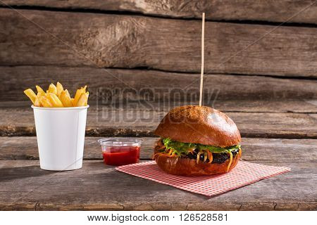Burger on stick with fries. Fresh hamburger on wooden table. Juicy lettuce and hearty meat. Best dish in local bistro.