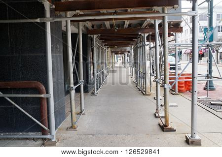 JOLIET, ILLINOIS / UNITED STATES - APRIL 12, 2015: Pedestrians may walk through a tunnel below a scaffold during renovation work on the historic Rialto Square Theater in downtown Joliet.
