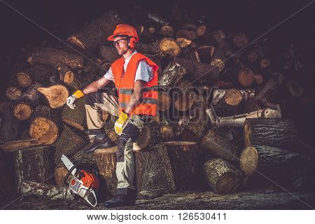Satisfied Lumber Worker. Timber Industry Concept Photo. Caucasian Lumber Worker with Wood Cutter Relaxing After Hard Working Day.