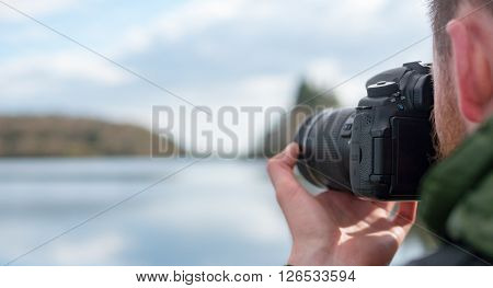 A landscape photograph of a photographer taking a picture of a resivior surrounded beautiful countryside located in Cornwall and Devon.