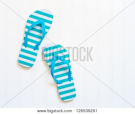 Blue and white beach sandals commonly call flip flops.