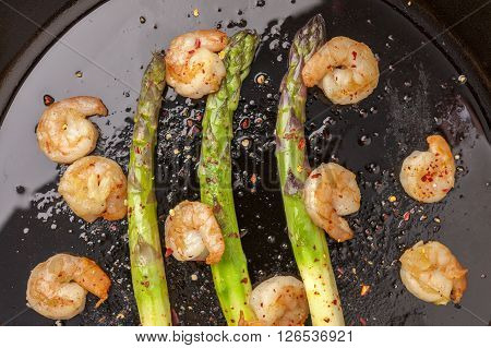 Shrimp and asparagus in a skillet topped with crushed red peppers.