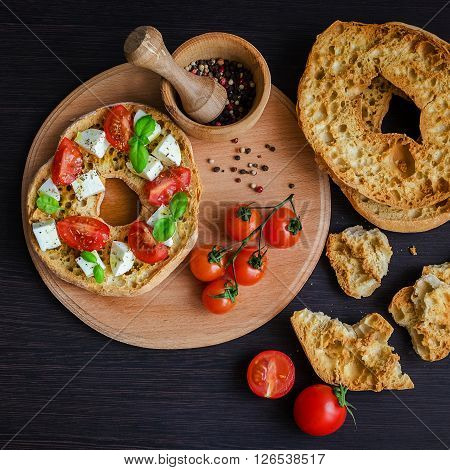 Italian appetizer Friselle. Italian dried bread Friselle on wooden board with tomatoes cherry, basil and peppercorns. Italian food. Healthy vegetarian food. Antipasti concept.