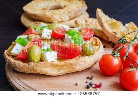 Italian appetizer Friselle. Italian dried bread Friselle on wooden board with tomatoes cherry, basil and pepper. Italian food. Healthy vegetarian food. Selective focus.