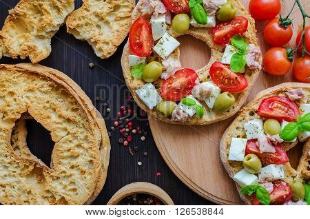 Italian appetizer Friselle. Italian dried bread Friselle on wooden board with tomatoes cherry, olives, tuna, basil and peppercorns. Italian food. Healthy vegetarian food. Antipasti concept.