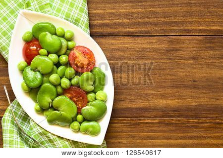 Broad bean green pea and cherry tomato salad photographed overhead on dark wood with natural light
