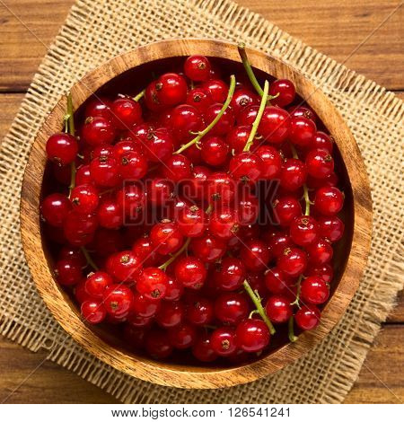 Raw red currants (lat. Ribes rubrum) in wooden bowl photographed overhead on dark wood with natural light (Selective Focus Focus on the top of the red currants)