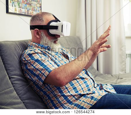 Senior Caucasian man touch something in virtual reality wearing headset glasses