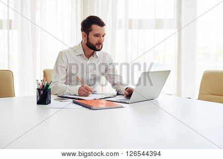 Beard man working on his laptop and writing some data in a pad  in the white office