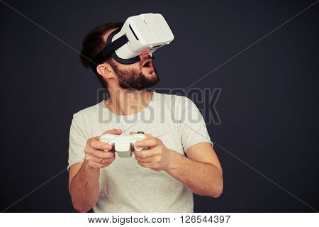 Man is playing on the joystick and looking up in virtual reality, on black background