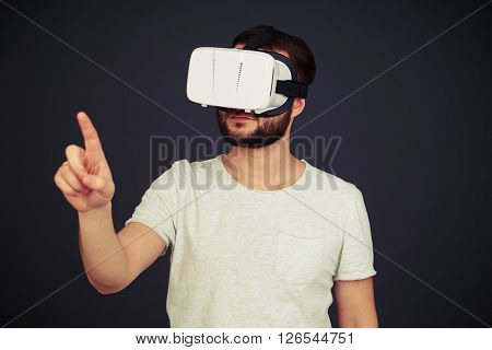 Man touch something with his right hand using virtual reality glasses, on black background