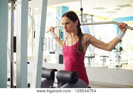 Pretty Caucasian girl in sportswear is working out pull-down machine in gym