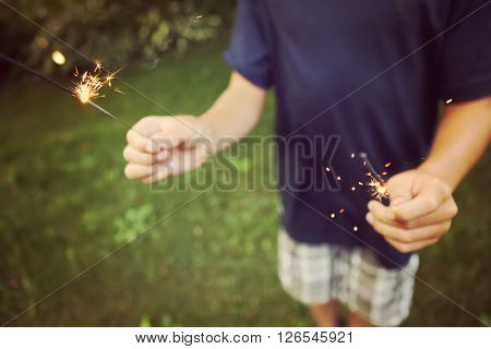 Child holding sparklers, shallow focus, focused on sparks
