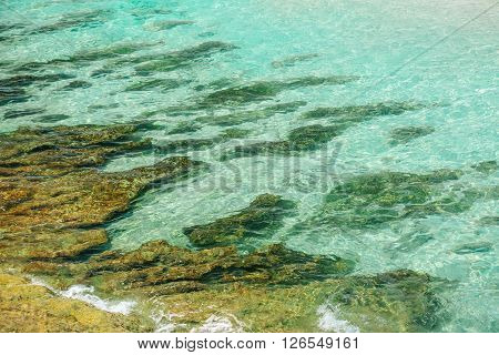 Abstract view of seashore ocean bottom through beautiful azure clear water with various golden colored stones
