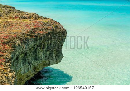 fragment of cliff sitting in turquoise charming clear Atlantic ocean water background