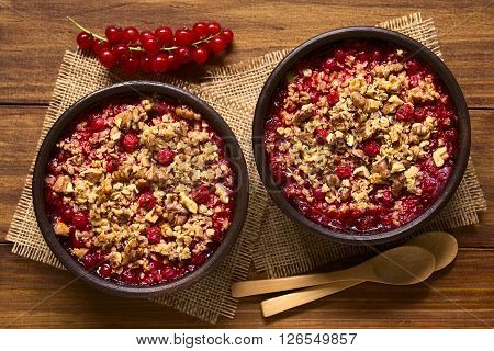 Redcurrant crumble or crisp with oatmeal and walnut on top baked in rustic bowls photographed overhead on dark wood with natural light (Selective Focus Focus on the top of the crumbles)