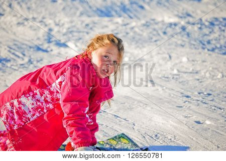 Young pretty girl in a pink winter coat on a sled with copy space.