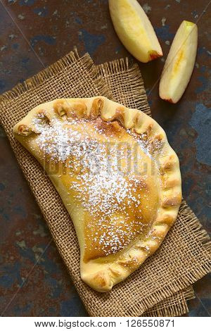 Chilean apple empanada with icing sugar photographed overhead on slate with natural light