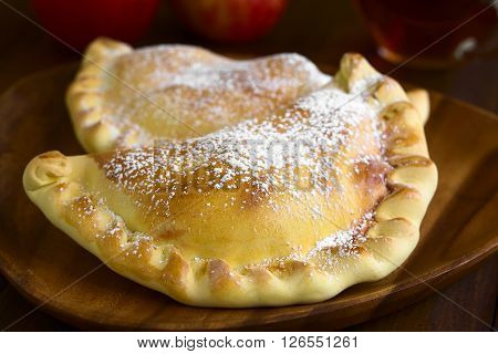 Chilean apple empanada with icing sugar photographed on dark wood with natural light (Selective Focus Focus one third into the image)
