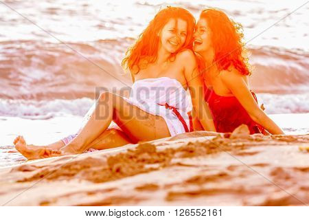 two young happy women, silhouettes on sunset sea background