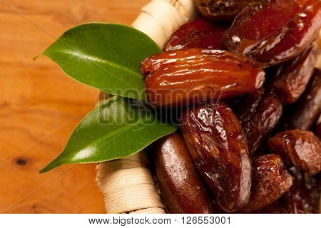 Sweet Dried Dates Fruit In Small Bowl, Mediterranean Desert On Wooden Surface.