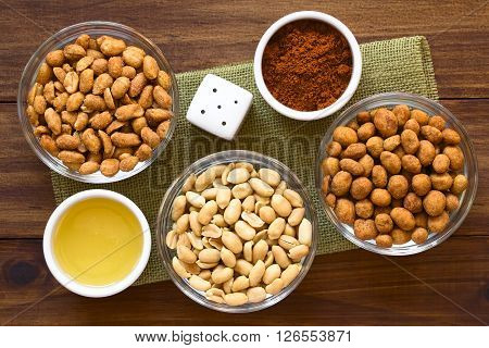 Peanut snacks in glass bowls. Peanuts with honey and salt salted peanuts peanuts roasted in a spicy coat. Photographed overhead on dark wood with natural light.