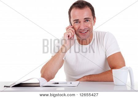 Smiling Middle-age Man Sitting At Desk On The Phone, On A White Background. Studio Shot