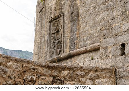 KOTOR, MONTENEGRO - AUGUST 30, 2009: Relief on the Kotor's old town outer defence wall of the south bastion