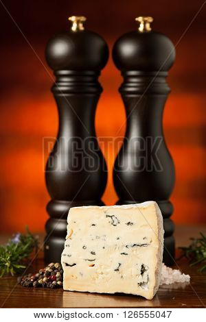 Piece Of Blue Cheese On A Wooden Table With Spices In Background