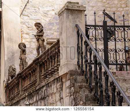 KOTOR MONTENEGRO - AUGUST 30 2009: Statues of children and a lion on the parapet of an elevated terraced entrance
