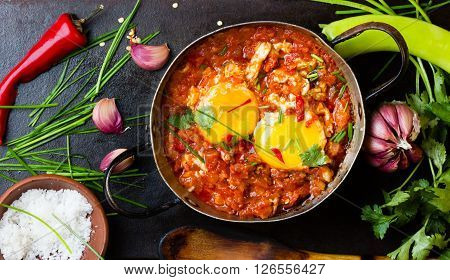 Mexican food - huevos rancheros. Eggs poached in tomato sauce salsa and other vegetables on black background. Top view